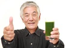 Homme japonais supérieur avec le jus de légumes vert Photo stock