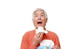 Homme japonais supérieur avec une allergie éternuant dans le tissu Images libres de droits