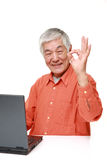 Homme japonais supérieur avec une allergie éternuant dans le tissu Image stock