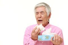 Homme japonais supérieur avec une allergie éternuant dans le tissue  Images stock