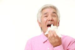 Homme japonais supérieur avec une allergie éternuant dans le tissue  Photo libre de droits
