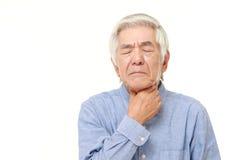 Homme japonais supérieur ayant la douleur de gorge Images stock