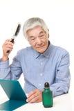 homme japonais supérieur employant le restaurateur de cheveux Photo stock