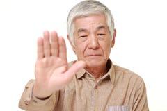 Homme japonais supérieur faisant le geste d'arrêt Image stock