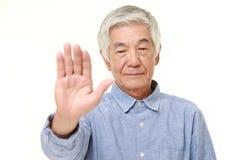 Homme japonais supérieur faisant le geste d'arrêt Photos stock