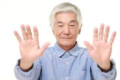 Homme japonais supérieur faisant le geste d'arrêt Photo libre de droits