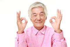 Homme japonais supérieur montrant le signe parfait Images stock