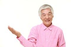 Homme japonais supérieur présent et montrant quelque chose Photographie stock libre de droits