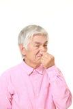 Homme japonais supérieur tenant son nez en raison d'une mauvaise odeur Photographie stock libre de droits