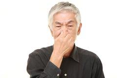 Homme japonais supérieur tenant son nez en raison d'une mauvaise odeur Photos stock