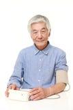 Homme japonais supérieur vérifiant sa tension artérielle Photos libres de droits