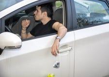 Homme jetant des ordures en l'air de fenêtre de voiture ouverte photographie stock