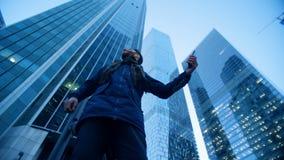 Homme jetant un coup d'oeil autour des gratte-ciel faisant un appel visuel Tir épique de caméra de cinéma banque de vidéos