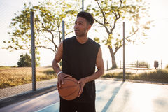 Homme jouant au basket-ball Compétitions sportives, jeu, homme avec la boule sur le terrain de basket, visage heureux, rire, attr Images stock