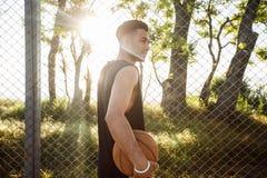 Homme jouant au basket-ball Compétitions sportives, jeu, homme avec la boule sur le terrain de basket, visage heureux, rire, attr Photographie stock libre de droits
