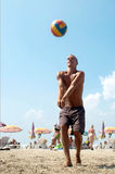 Homme jouant au volleyball sur une plage. Photographie stock libre de droits