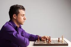 Homme jouant aux échecs sur le fond blanc Photos libres de droits