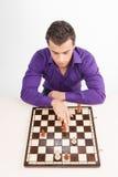 Homme jouant aux échecs sur le fond blanc Image libre de droits