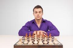 Homme jouant aux échecs sur le fond blanc Photographie stock libre de droits