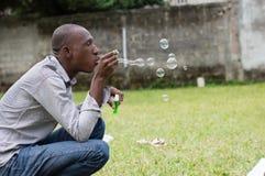 Homme jouant avec des bulles de savon photographie stock libre de droits