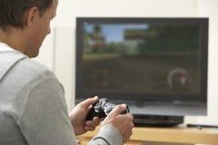Homme jouant avec la console de jeu Image stock