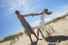 Homme jouant avec la fille à la plage image libre de droits