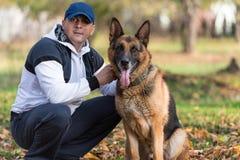 Homme jouant avec le berger allemand In Park de chien Image stock