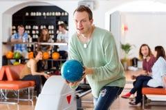 Homme jouant dans le bowling au club Photographie stock libre de droits