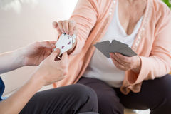 Homme jouant des cartes avec une femme plus âgée Images libres de droits