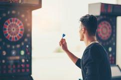 Homme jouant des dards d'un tir de jeu Photo stock
