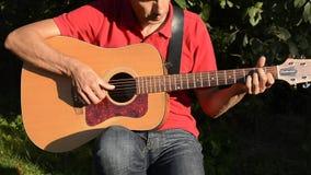Homme jouant la guitare acoustique à l'extérieur banque de vidéos