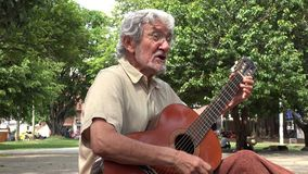 Homme jouant la guitare acoustique et le chant banque de vidéos
