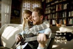 Homme jouant la guitare acoustique sur le sofa pour sa jeune belle femme photos stock