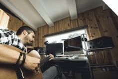 Homme jouant la guitare dans un studio d'enregistrement Musique de composition de guitariste de concept images libres de droits