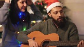 Homme jouant la guitare et chantant la séance sur le plancher près de l'arbre de Noël dans la chambre moderne Les couples heureux banque de vidéos