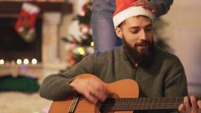 Homme jouant la guitare et chantant la séance sur le plancher près de l'arbre de nouvelle année dans la chambre moderne Femme ave banque de vidéos
