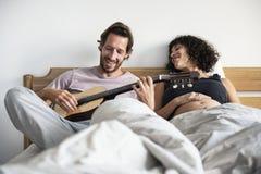 Homme jouant la guitare pour l'épouse enceinte images stock