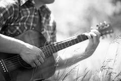 Homme jouant la guitare sur le pique-nique Image stock