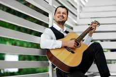 Homme jouant la guitare sur les escaliers photographie stock libre de droits