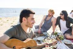 Homme jouant la guitare sur la partie de plage Photo libre de droits