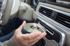 Homme jouant la musique en CD DE HAUTE FIDÉLITÉ de insertion automobile hic dans sa fente de lecteur de CD photographie stock libre de droits
