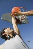 Homme jouant le basket-ball avec l'ami contre le ciel Photo stock