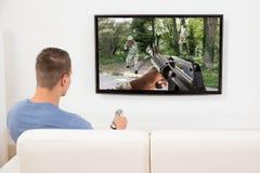 Homme jouant le jeu d'ordinateur à la télévision photos libres de droits