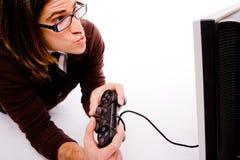 homme jouant le jeu vidéo latéral de pose Image stock