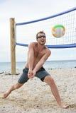 Homme jouant le match de volley de plage frappant la boule Image libre de droits
