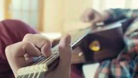 Homme jouant le mouvement lent de plan rapproché de guitare acoustique banque de vidéos