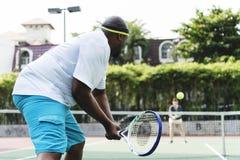 Homme jouant le tennis avec son amie Photographie stock libre de droits
