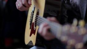 Homme jouant sur la guitare acoustique Plan rapproché des doigts sur la plate-forme et les ficelles banque de vidéos