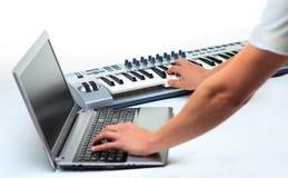 Homme jouant sur un synthétiseur Photographie stock libre de droits