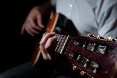 Homme jouant une guitare acoustique sur un fond foncé Jeu de la guitare image stock
